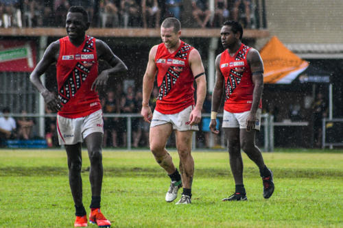 Paddy Heenan with former West Coast Eagles player Ashton Hams during round 15 of the NTFL. Dion Munkara is in the foreground.